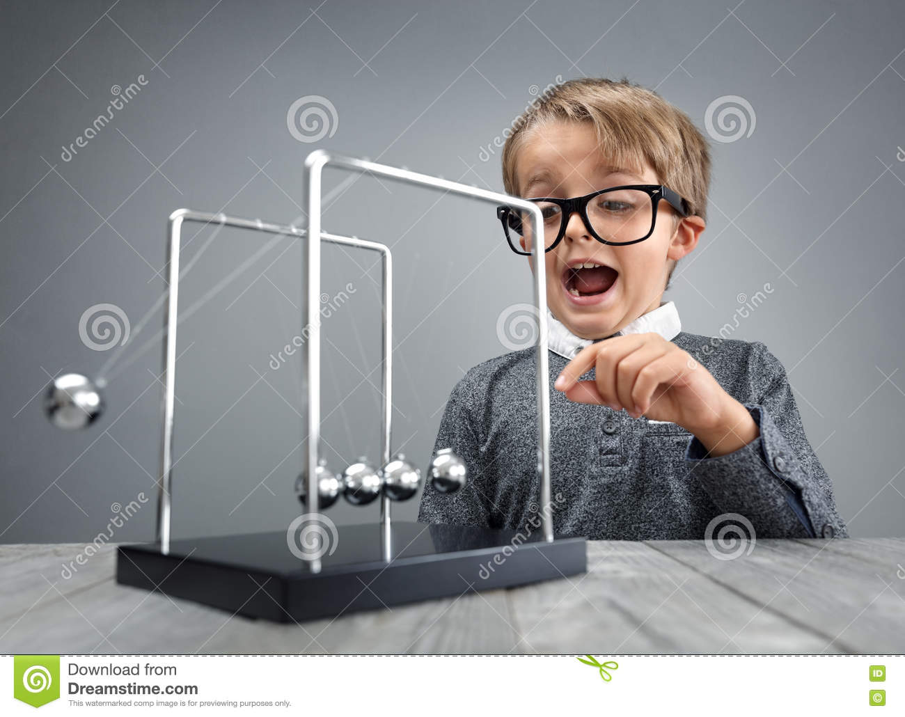 Physics and science education boy with Newton s cradle