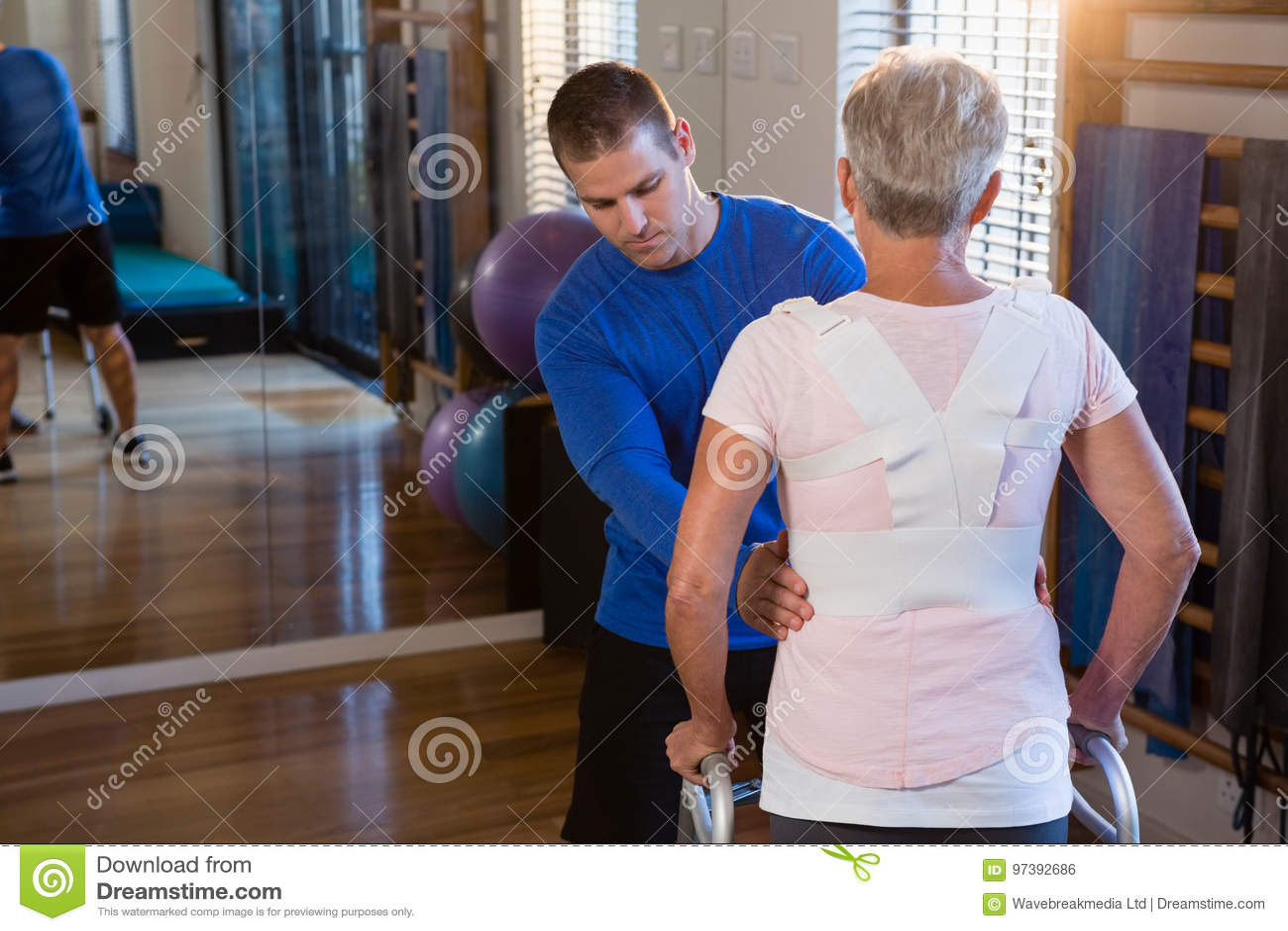 Physiothérapeute aidant le patient pour marcher avec le cadre de marche