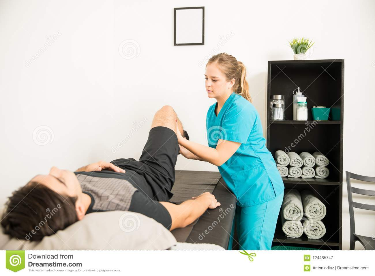 Physiothérapeute Helping Male Athlete avec l exercice de jambe