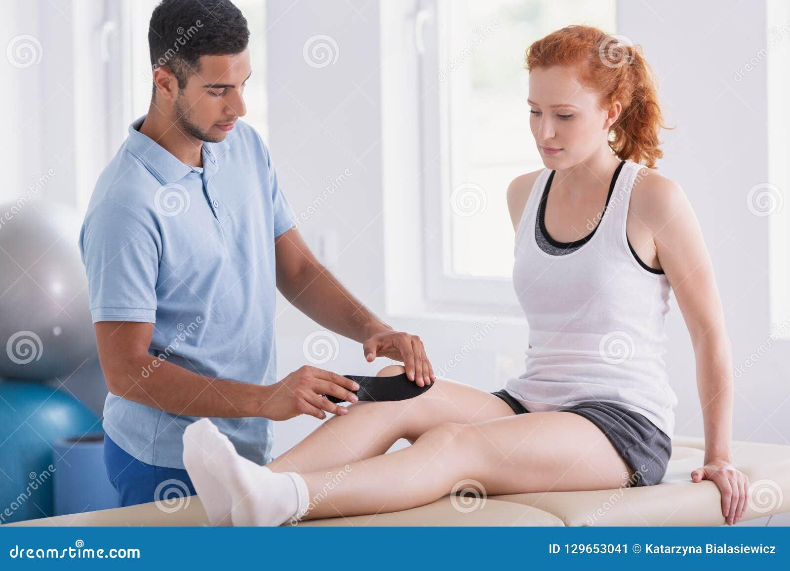 Physiotherapist kładzenia taśmy na pacjent nodze podczas kinesiotaping