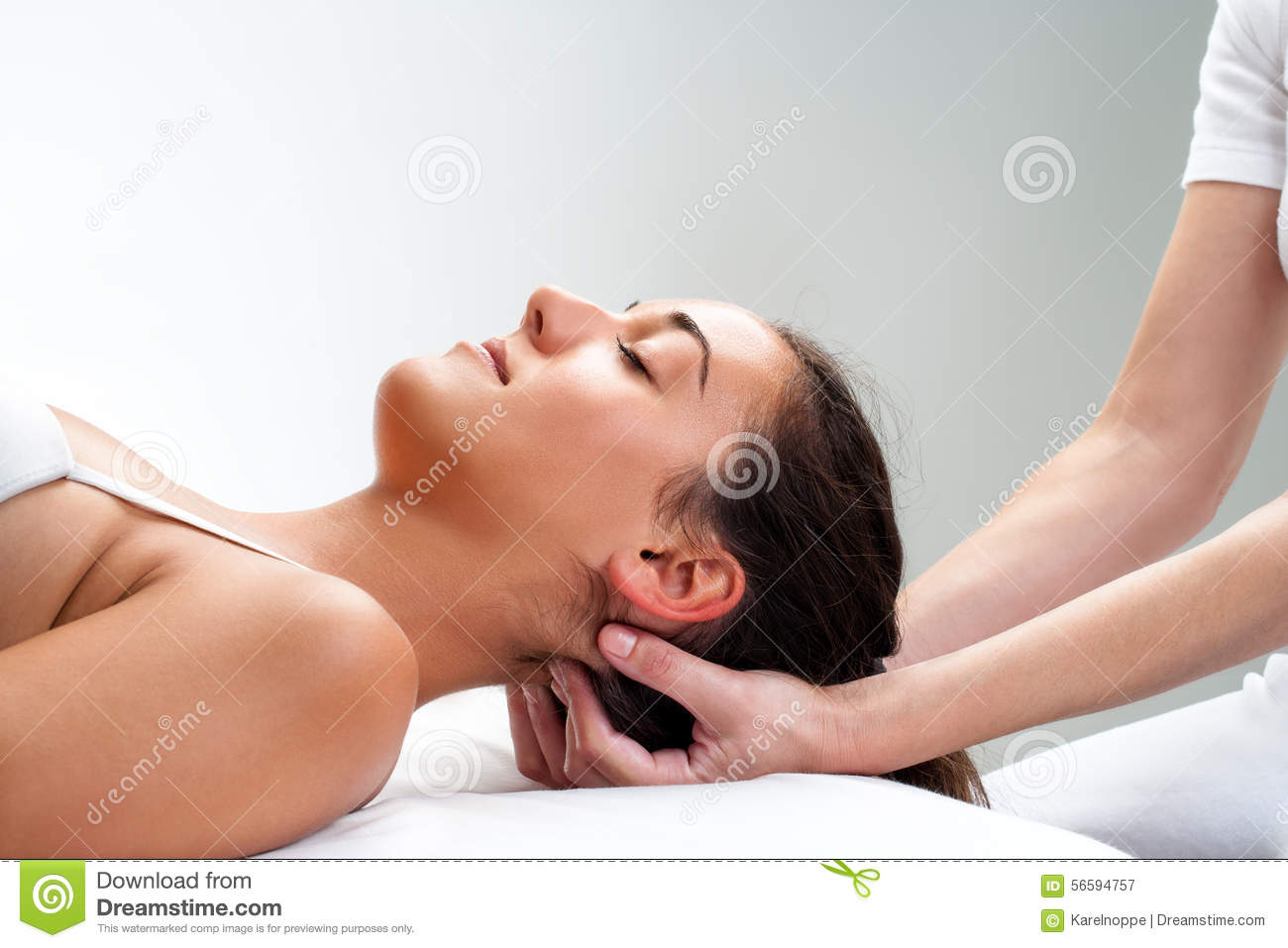 Physiotherapist pressing back of woman s head.