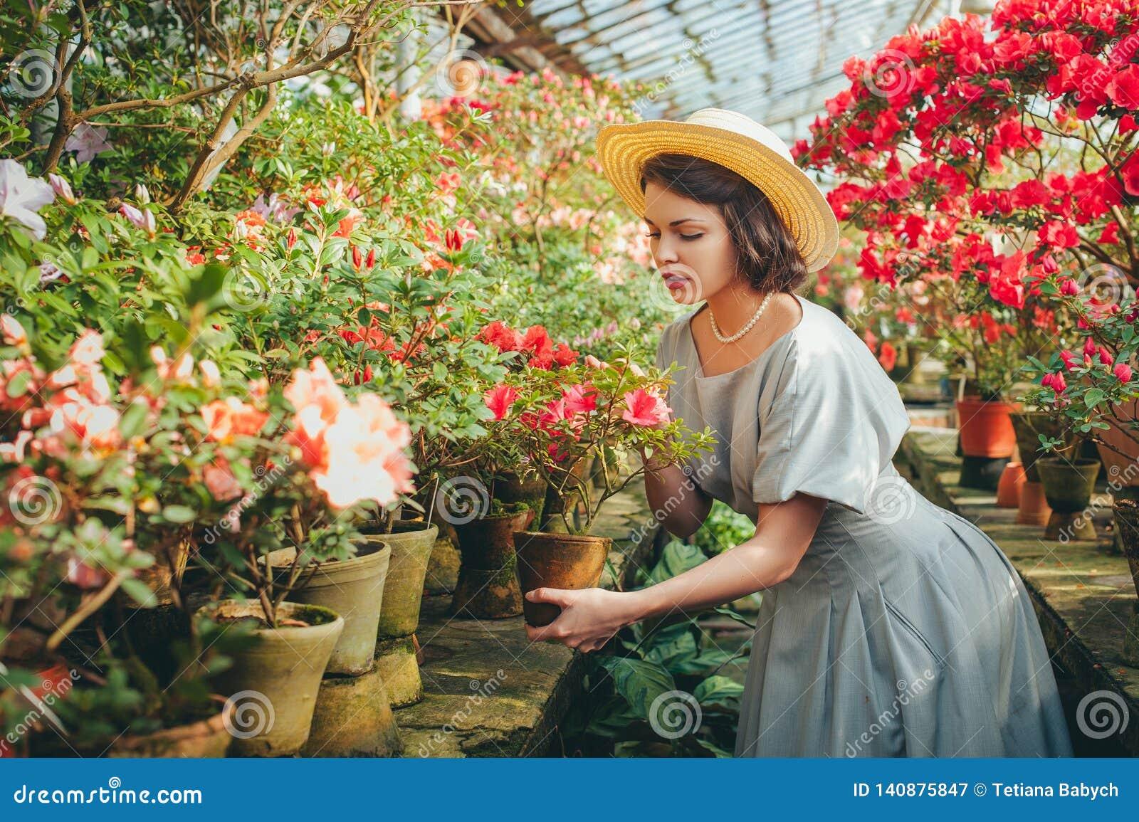 Piękna dorosła dziewczyna marzy w pięknym retro kapeluszu i sukni w azalii szklarni