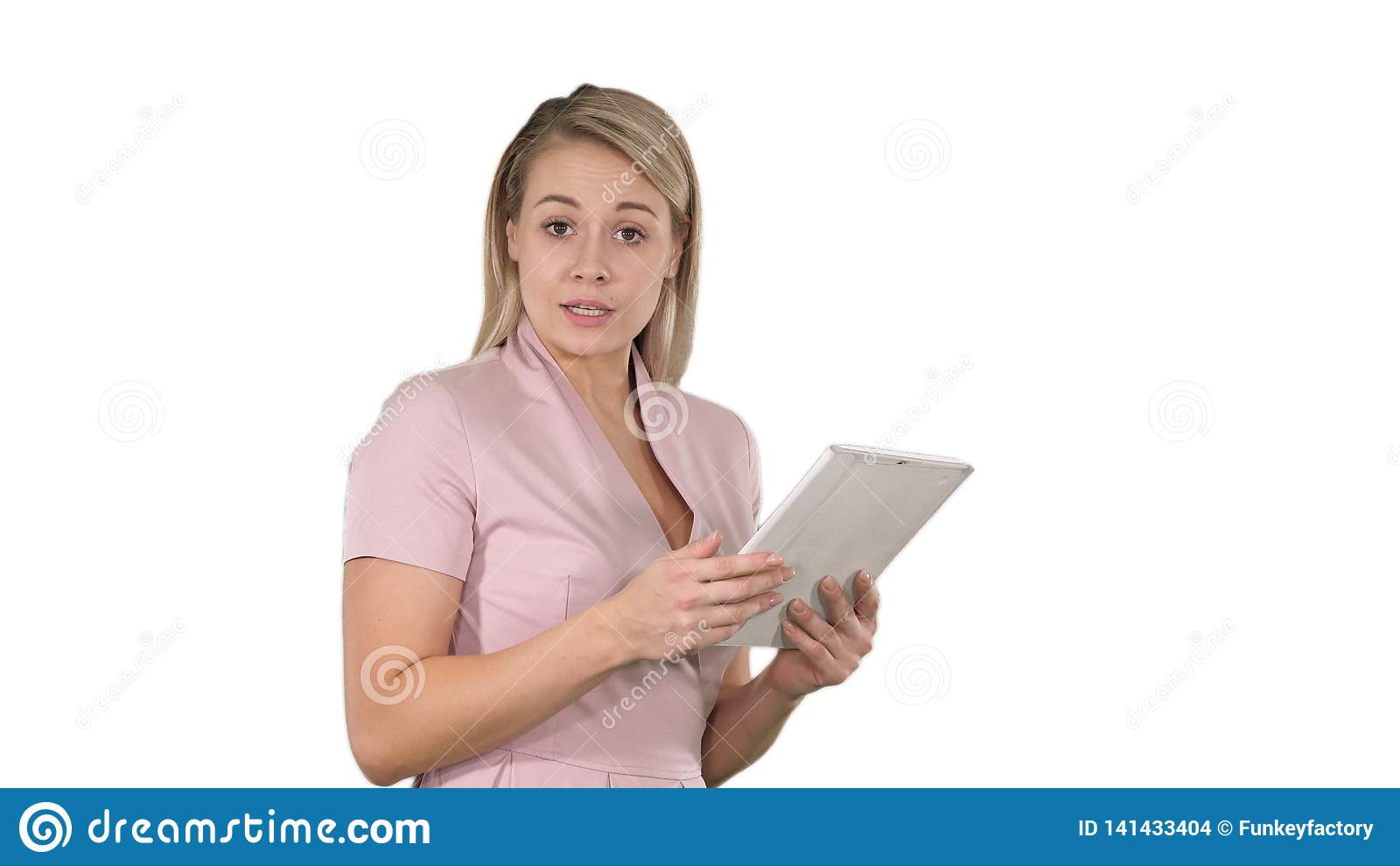 Piękna kobieta używa cyfrową pastylkę i opowiadający kamera na białym tle