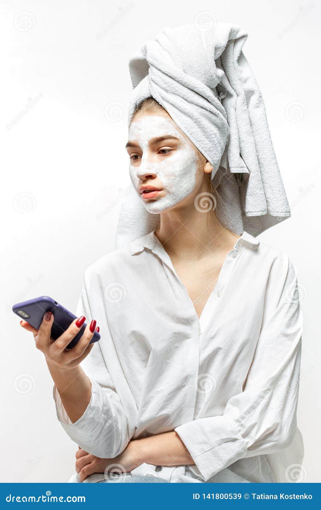 Piękna młoda kobieta ubierał w biel ubraniach z białym ręcznikiem na jej włosy i kosmetyk maska na jej twarzy trzyma wiszącą ozdo