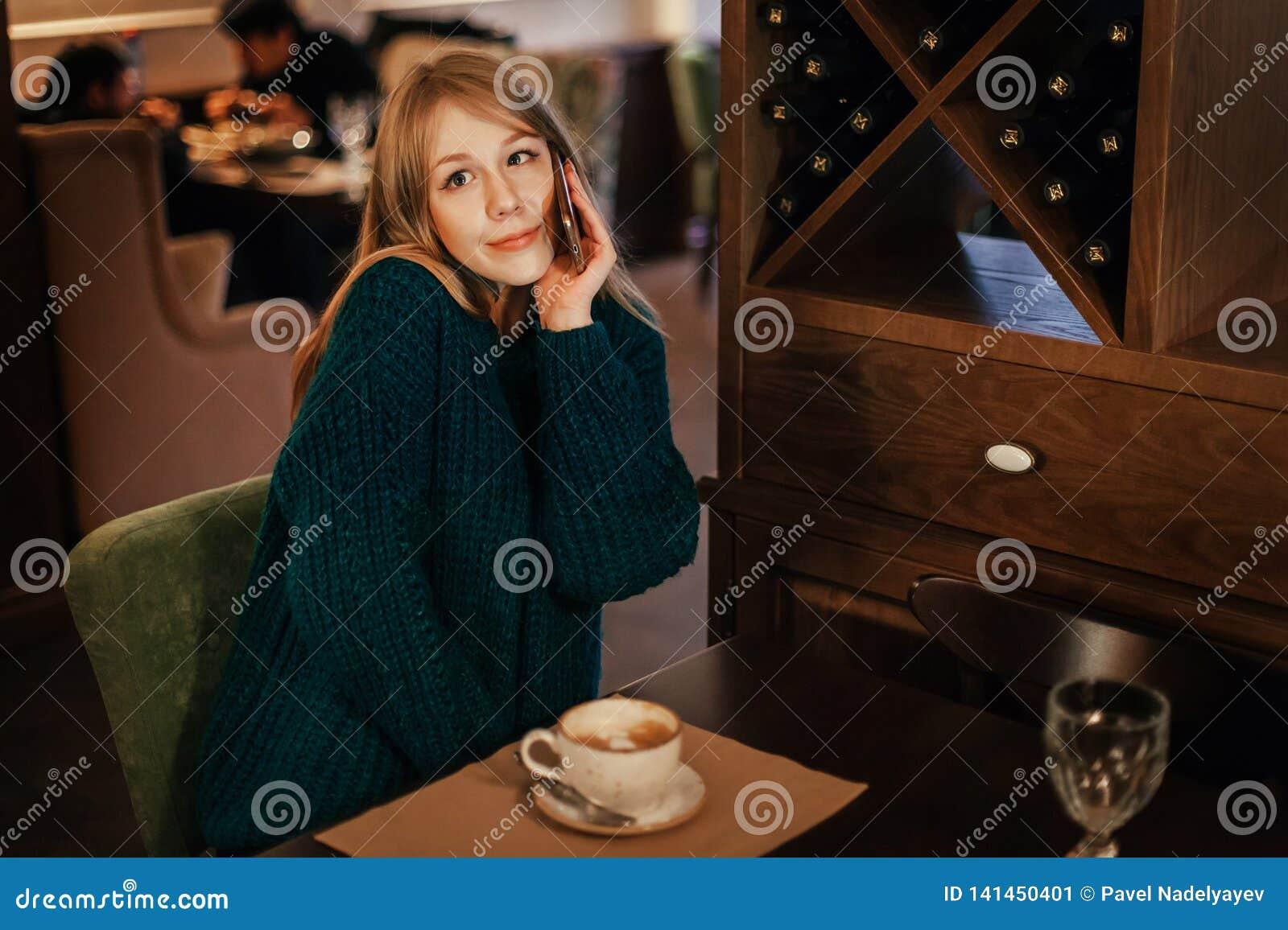 Piękna młodej kobiety blondynka pije kawę w restauracji zdziwiona emocja z telefonem kokietka