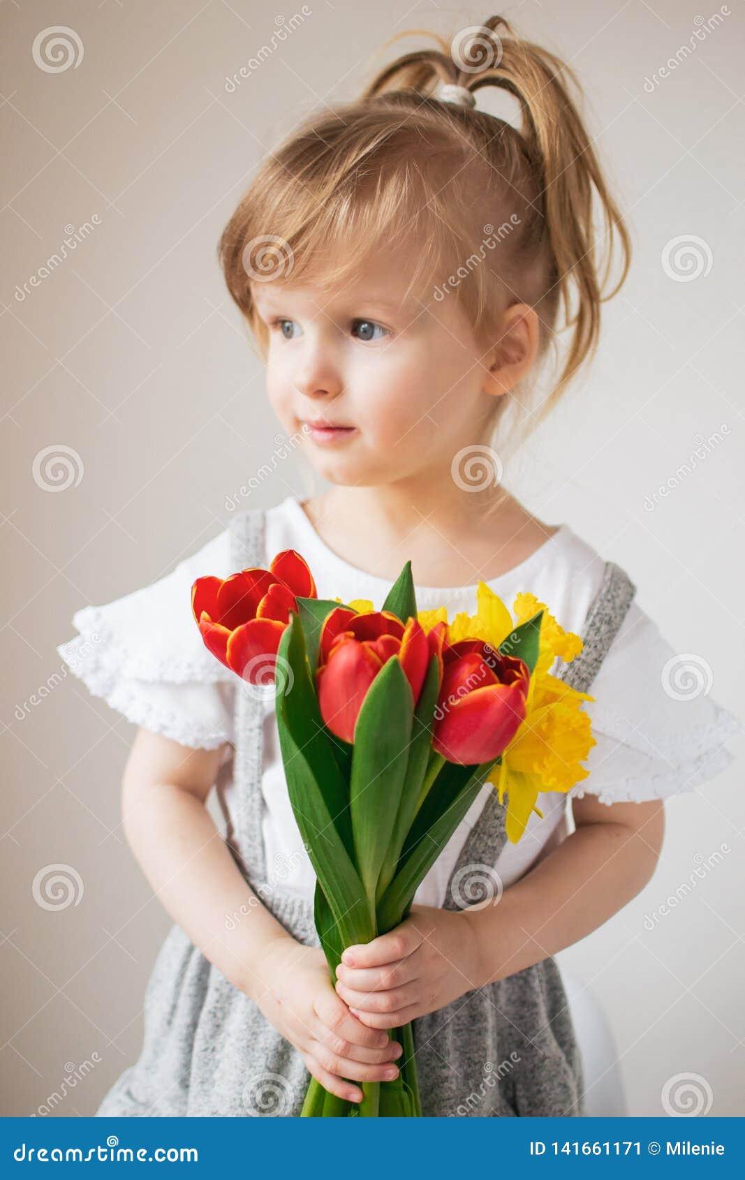 Piękna mała dziewczynka trzyma bukiet kwiaty