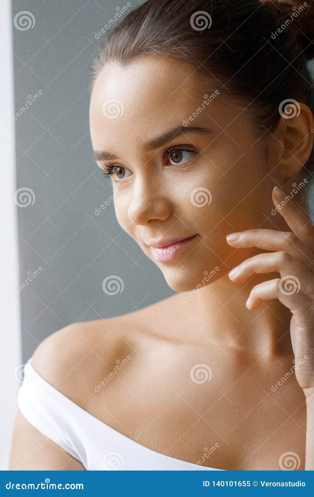 Piękna twarz młoda kobieta z kosmetyczną śmietanką na policzku Skóry opieki pojęcie Zbliżenie portret na popielatym tle