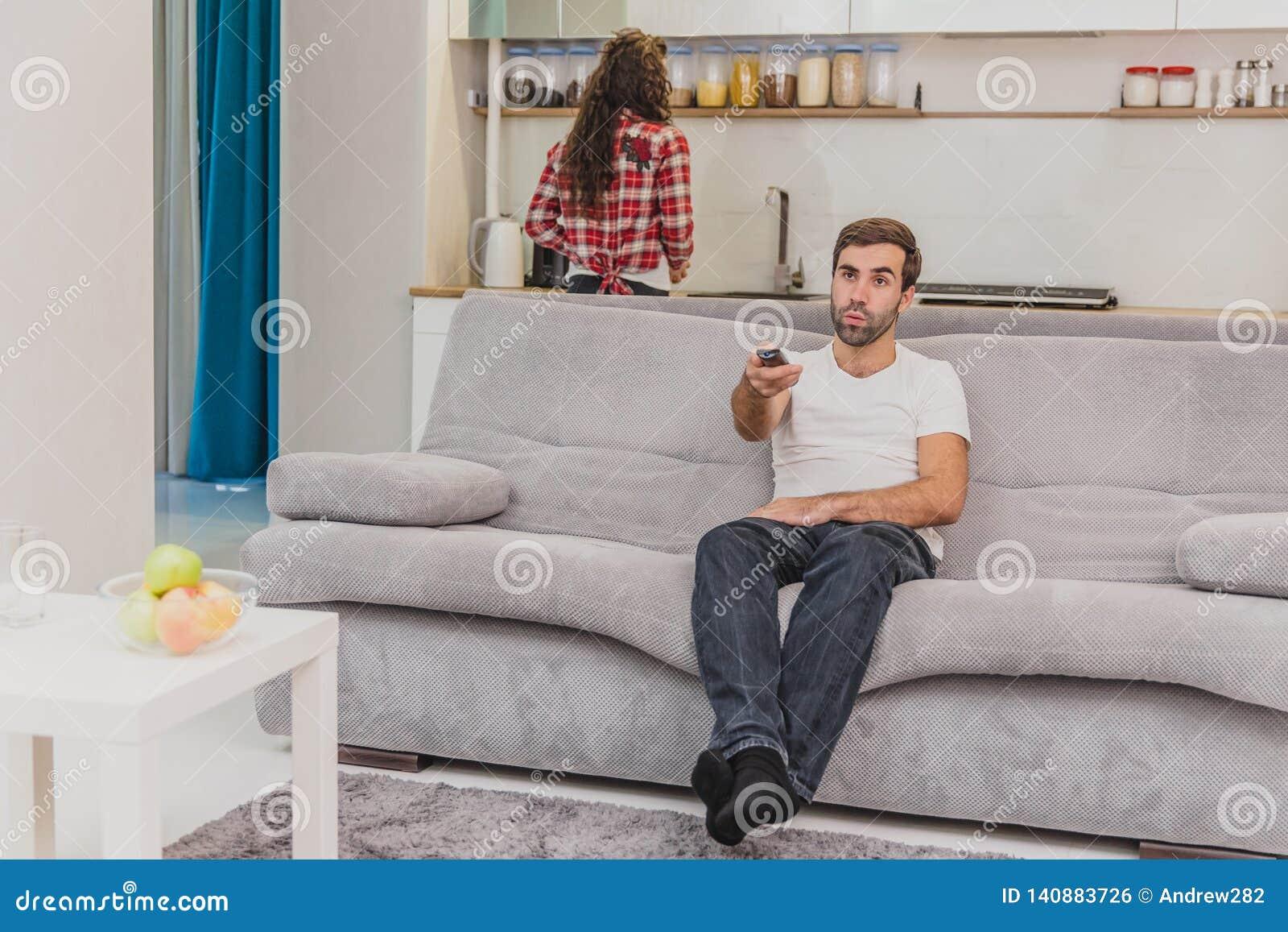 Piękny komicznie młody człowiek trzyma pilota do tv Podczas to TV ogląda podczas gdy siedzący na leżance przy