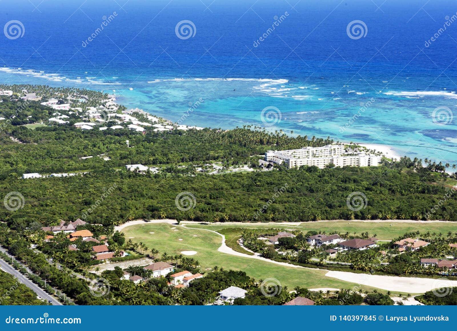 Piękny odgórny widok: turkusowy morze karaibskie, piaskowata plaża, palmowy gaj, hotele na jaskrawym słonecznym dniu