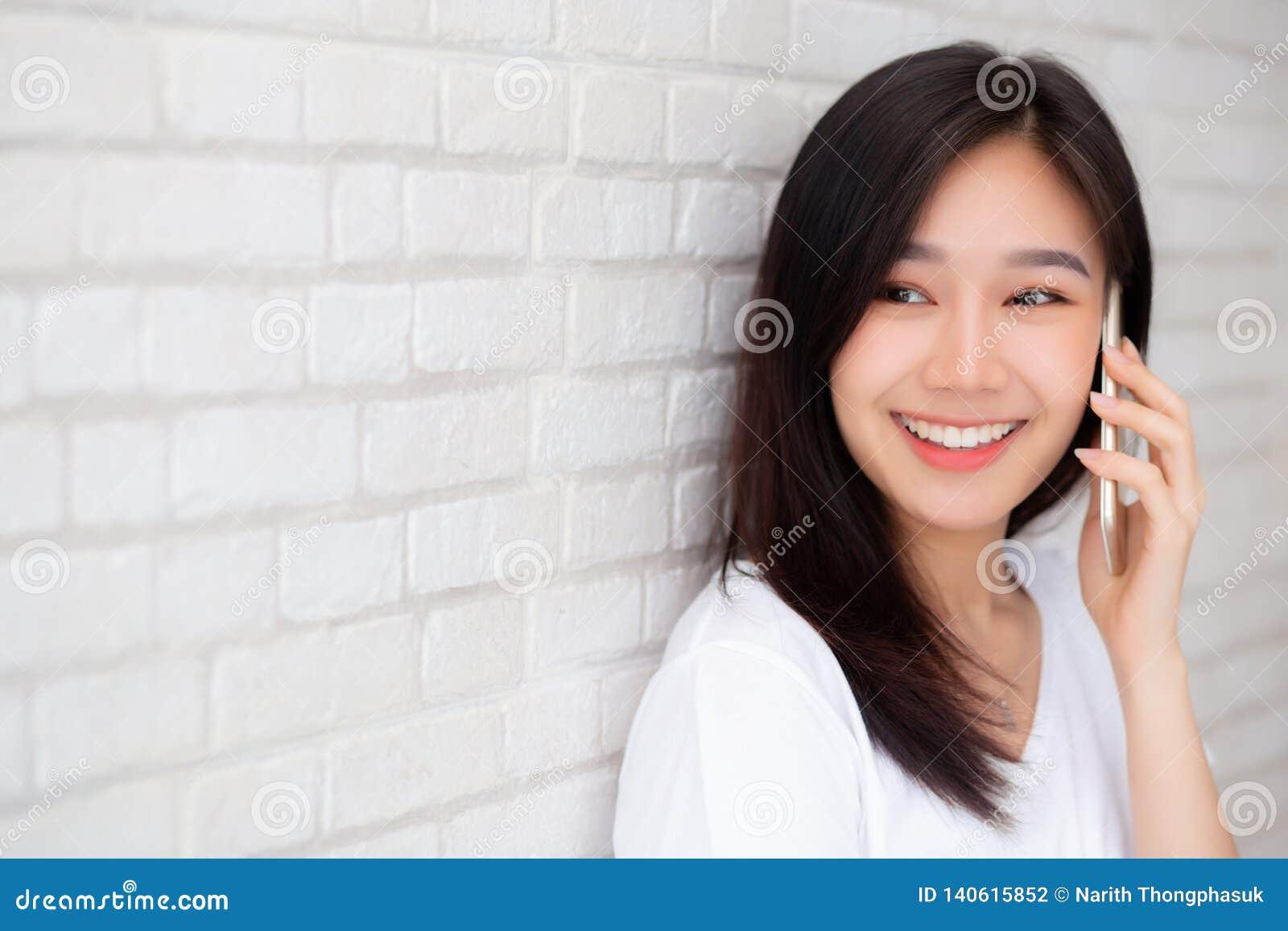 Piękny portret kobiety młodej azjatykciej rozmowy mądrze telefonu i uśmiechu pozycja na cementowym ceglanym tle