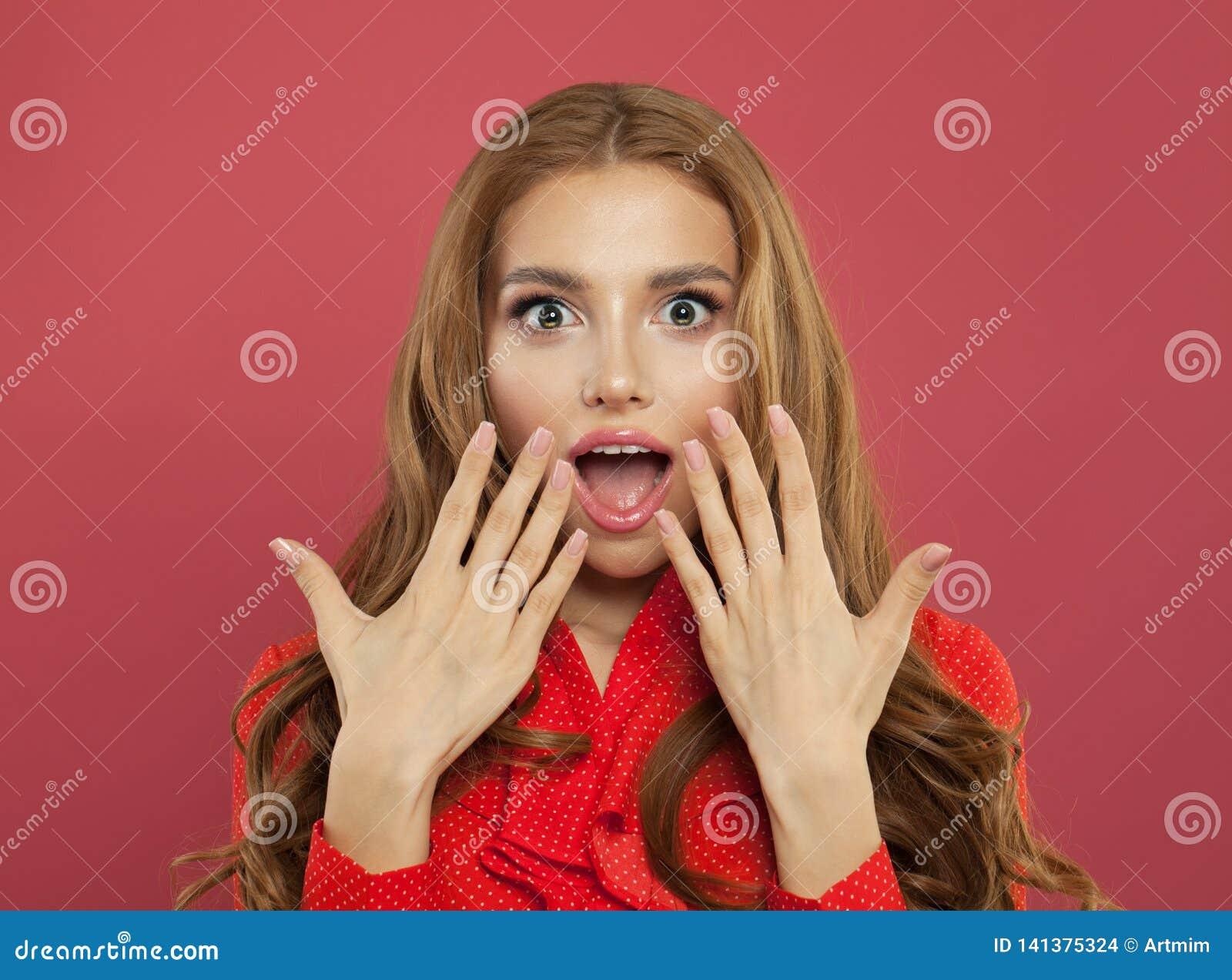Pięknych potomstw z podnieceniem zdziwiona kobieta z rozpieczętowanym usta na kolorowym jaskrawym różowym tle emoci mody model ta