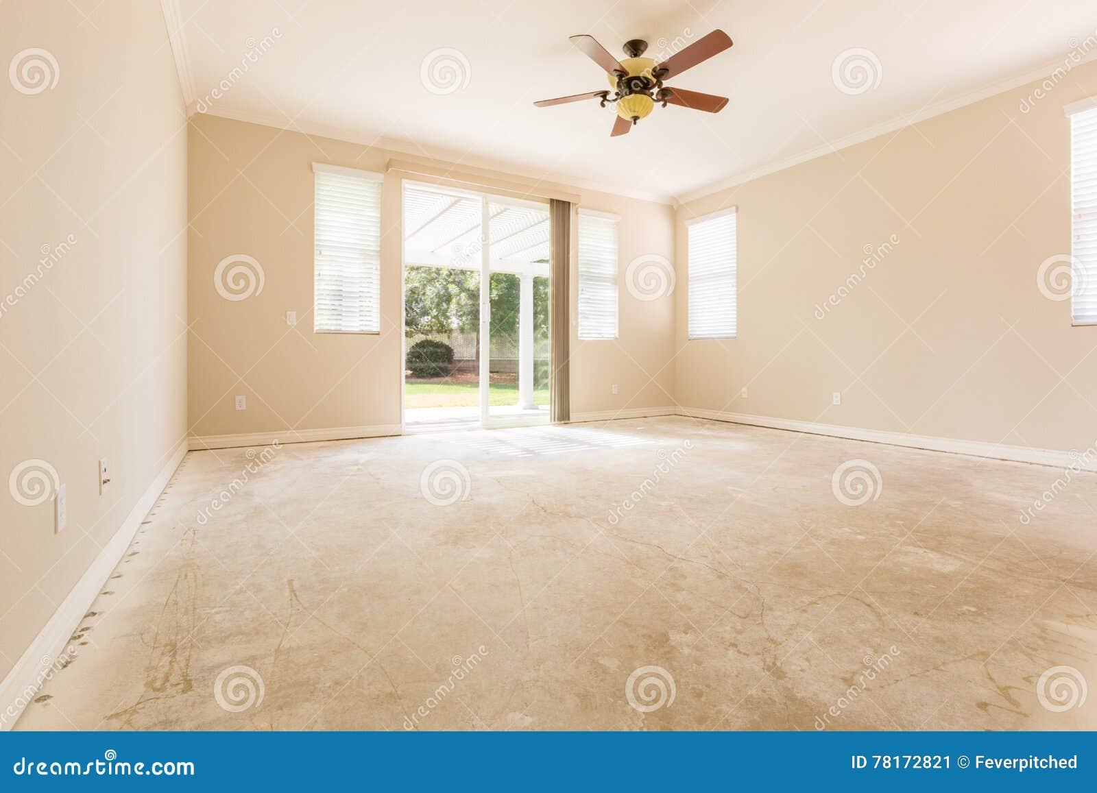 Pièce avec les planchers de ciment et la fan de plafond