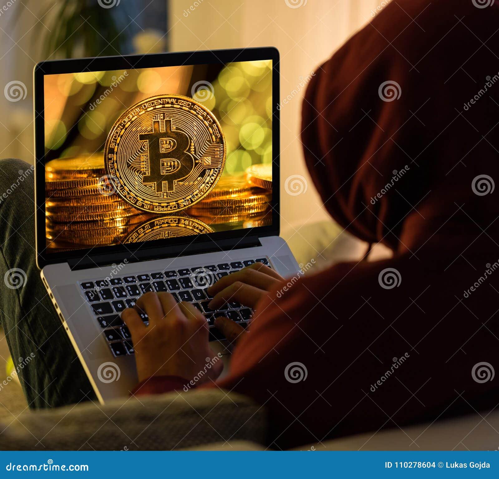 Pièce d or de Bitcoin et sittign anonyme de pirate informatique avec l ordinateur portable