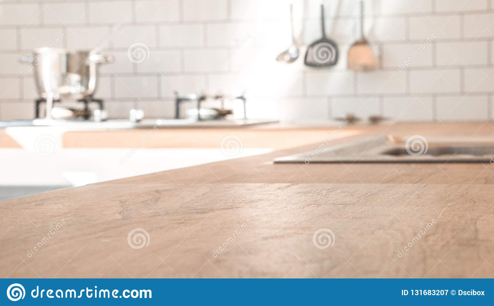 Pièce de cuisine et concept de fond - dessus en bois brun brouillé de comptoir de cuisine avec la belle pièce moderne de cuisine