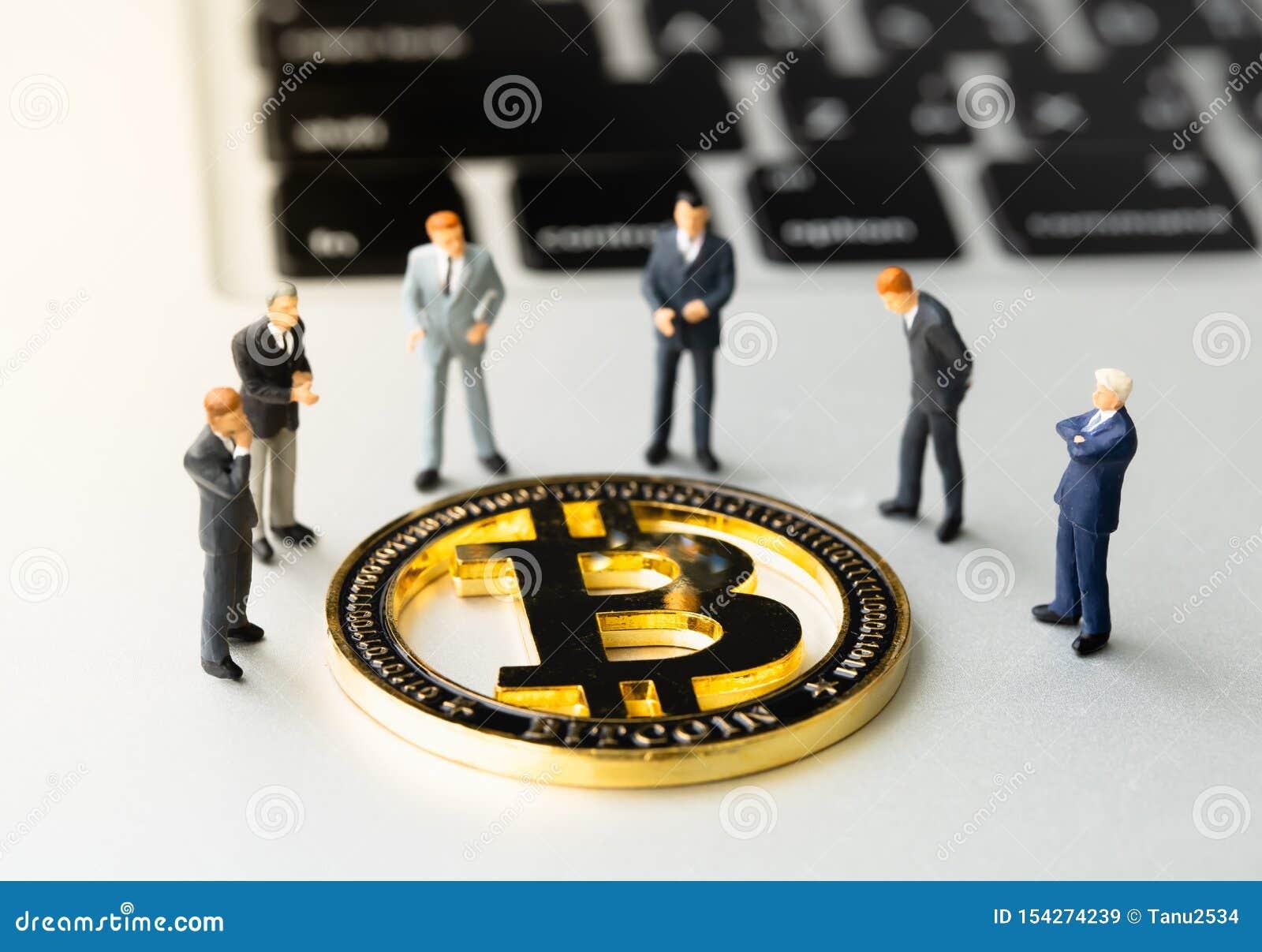 Pièce de monnaie et businessmans de Bitcoin BTC sur le carnet
