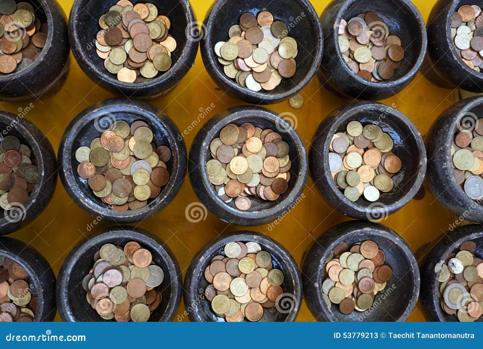 Pièce de monnaie thaïlandaise dans la cuvette de l aumône de moine bouddhiste