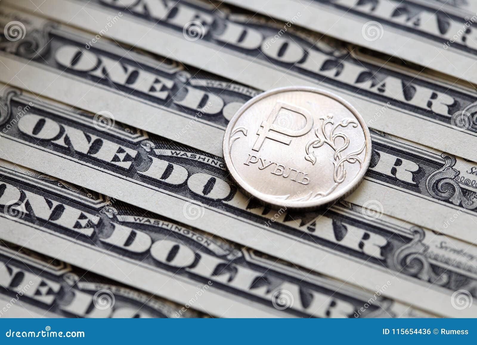 Pièce de rouble russe sur un fond de billets d un dollar