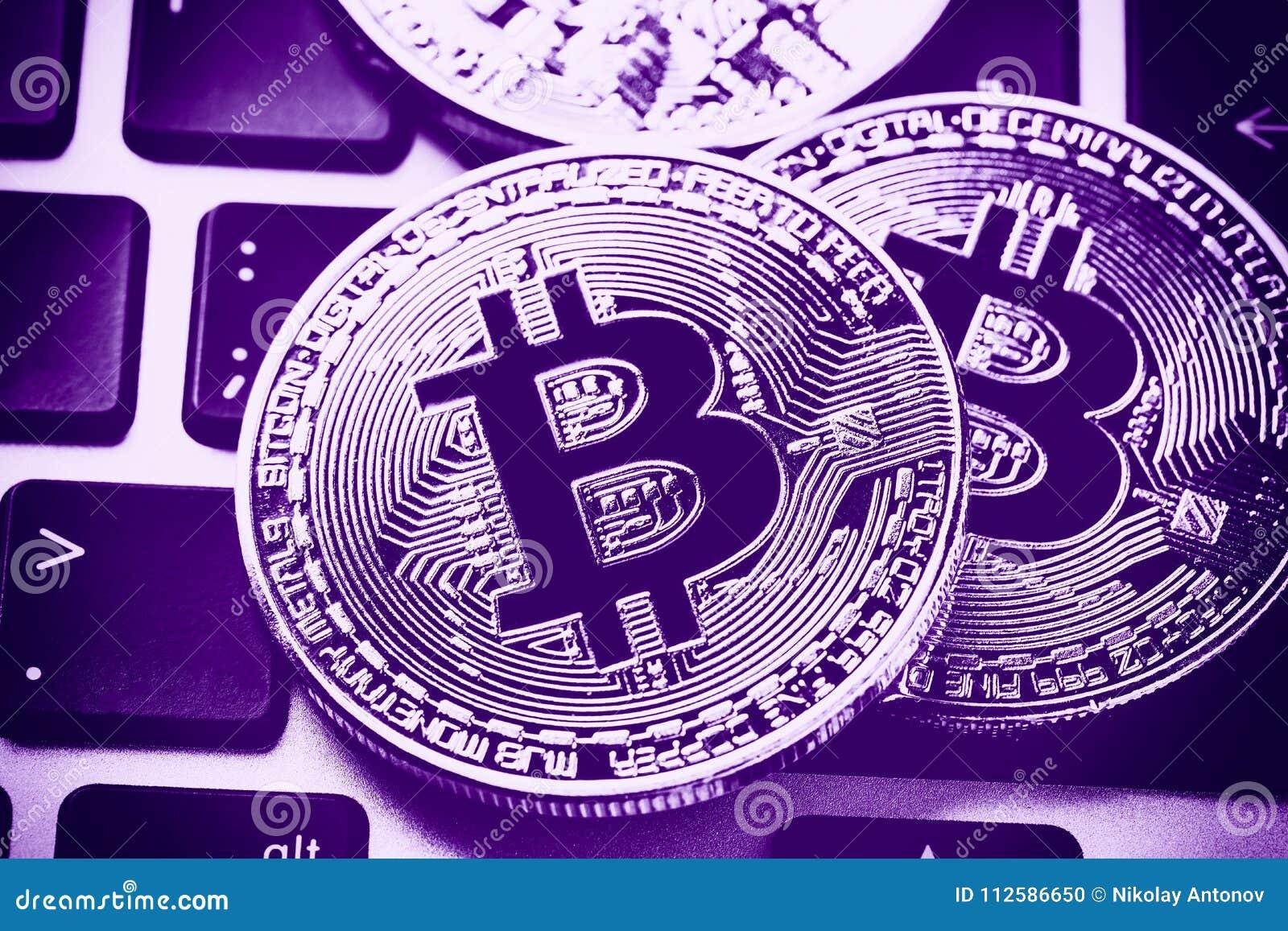 Pièces de monnaie de cryptocurrency de Bitcoin sur le clavier d ordinateur portable Fermez-vous vers le haut de l ultraviolet mod