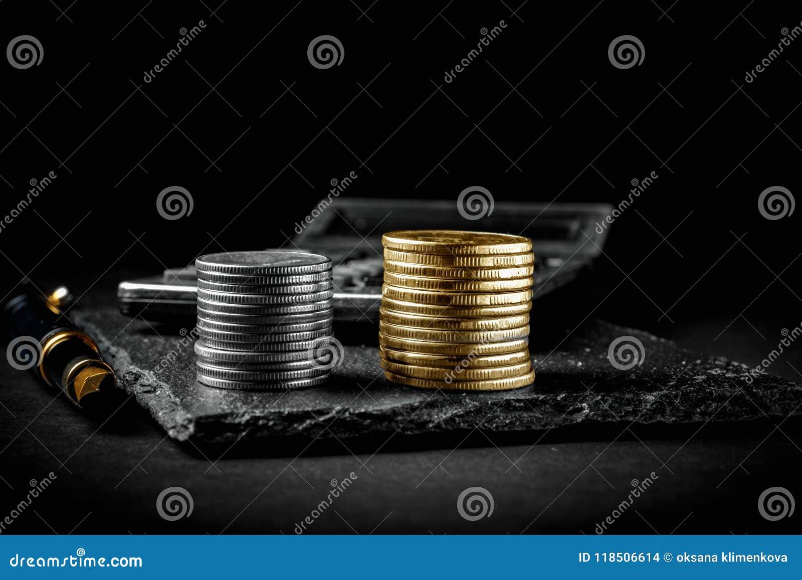 Pièces de monnaie d un stylo-plume, de calculatrice, argentées et d or Concept d affaires, de finances ou d investissement