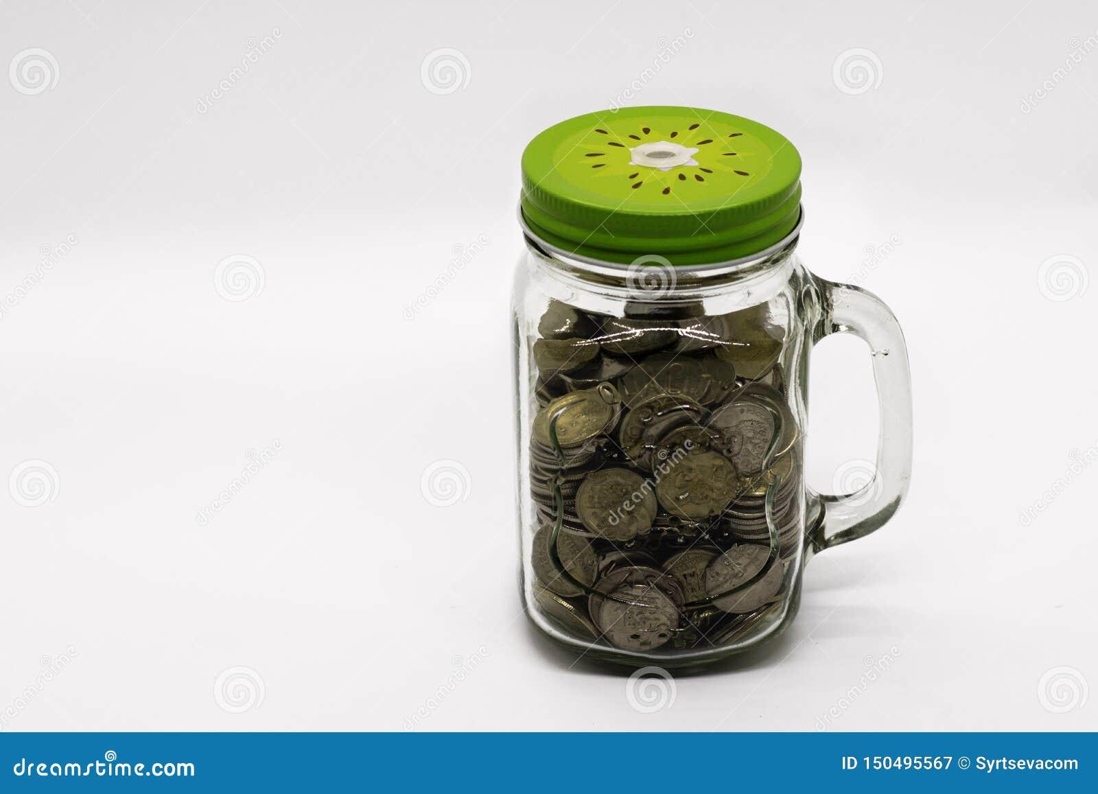 Pièces de monnaie en métal dans le pot en verre du pot de maçon sur le fond blanc