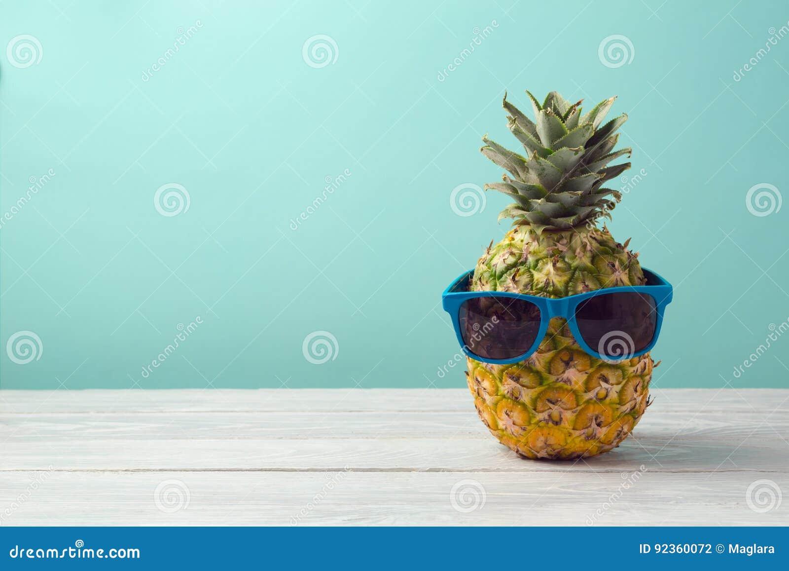 Piña con las gafas de sol en la tabla de madera sobre fondo de la menta Vacaciones de verano y partido tropicales de la playa