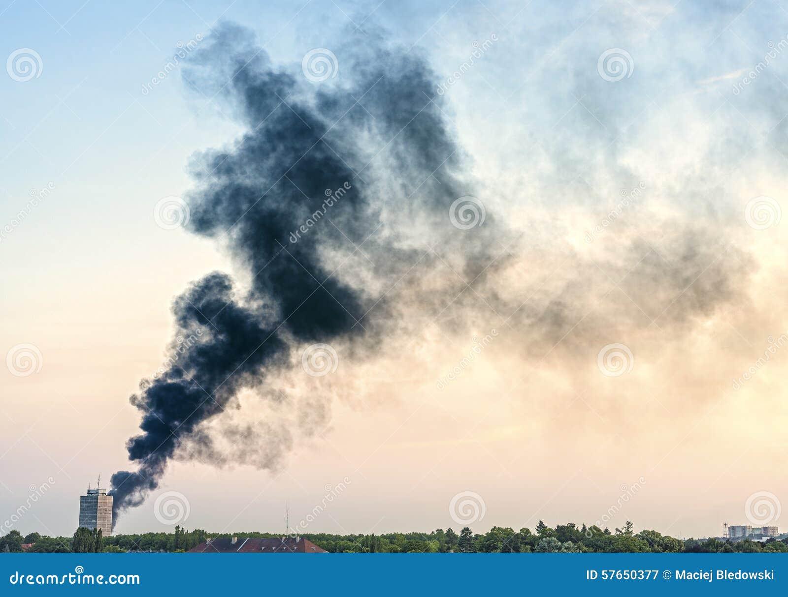 Pióropusz dym od ogienia nad miasto przy zmierzchem