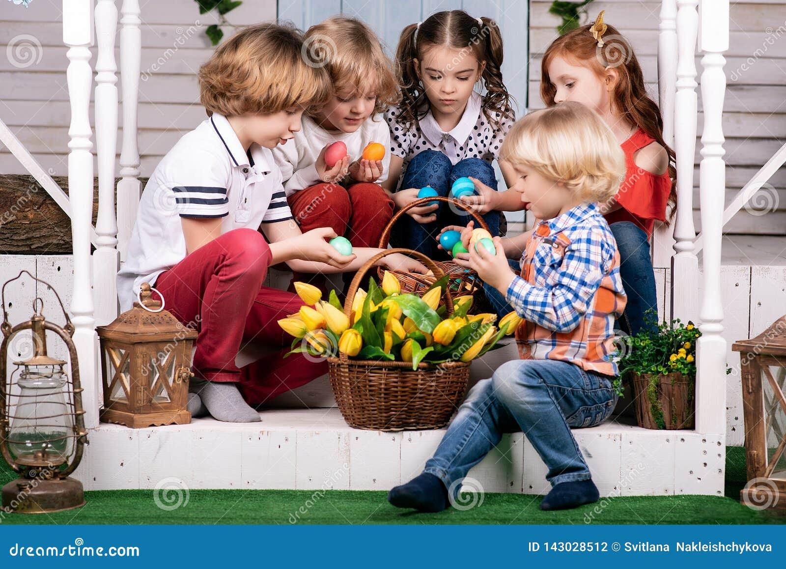 Pięć ślicznych dzieci siedzą na progu i biorą za kolorowych jajkach od kosza Wielkanoc
