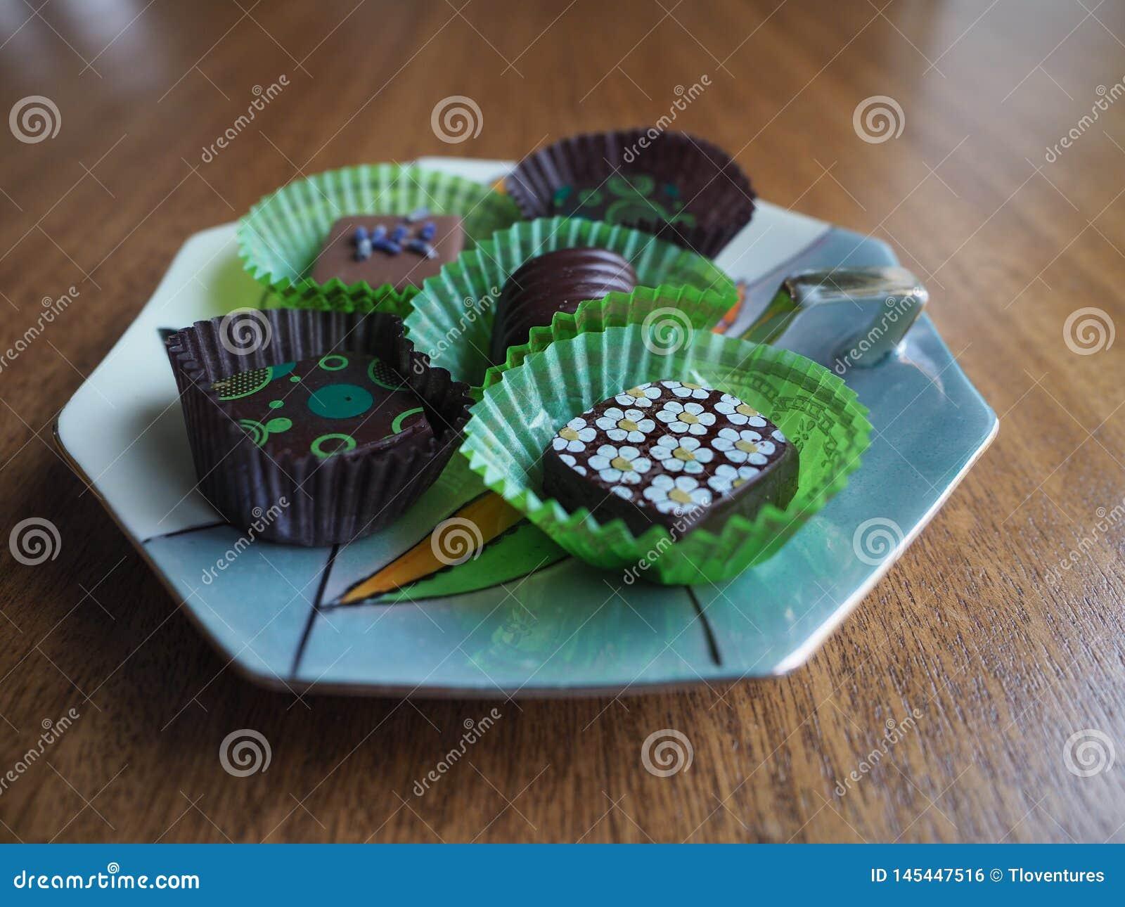 Pi?? Dekoruj?cych czekolad na porcelana cukierku naczyniu przy oko poziomem