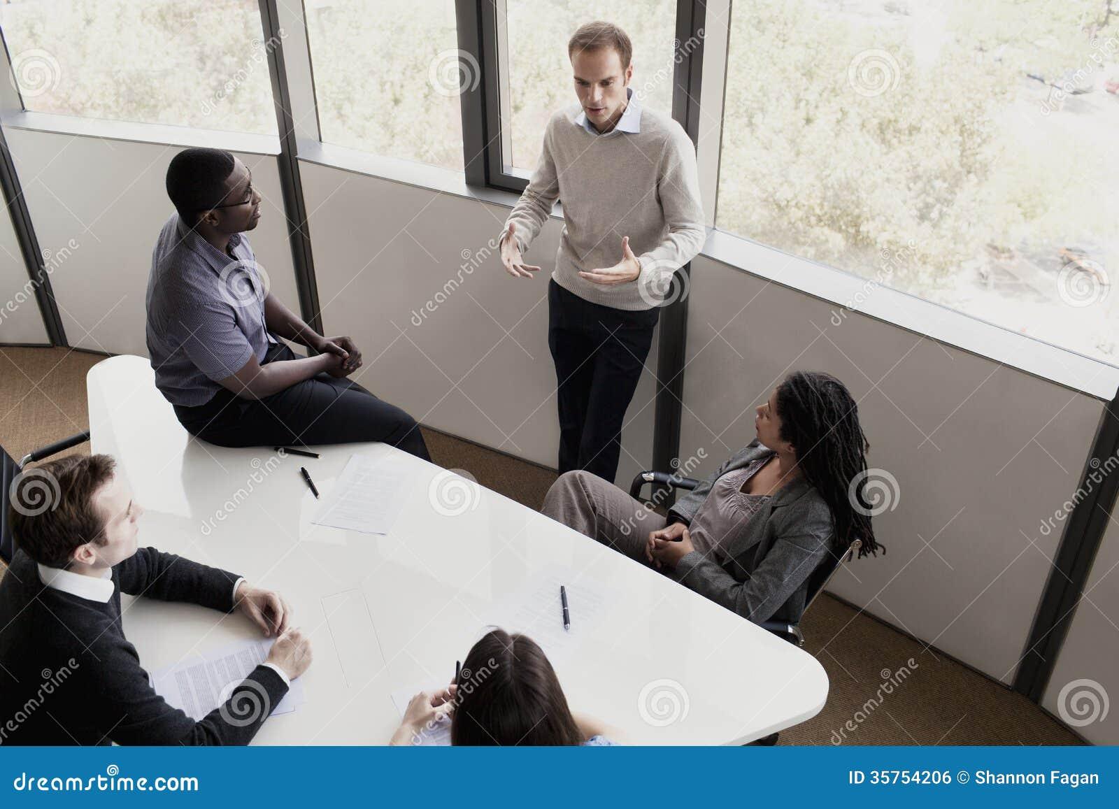 Pięć ludzi biznesu siedzi przy konferencyjnym stołem i dyskutuje podczas biznesowego spotkania