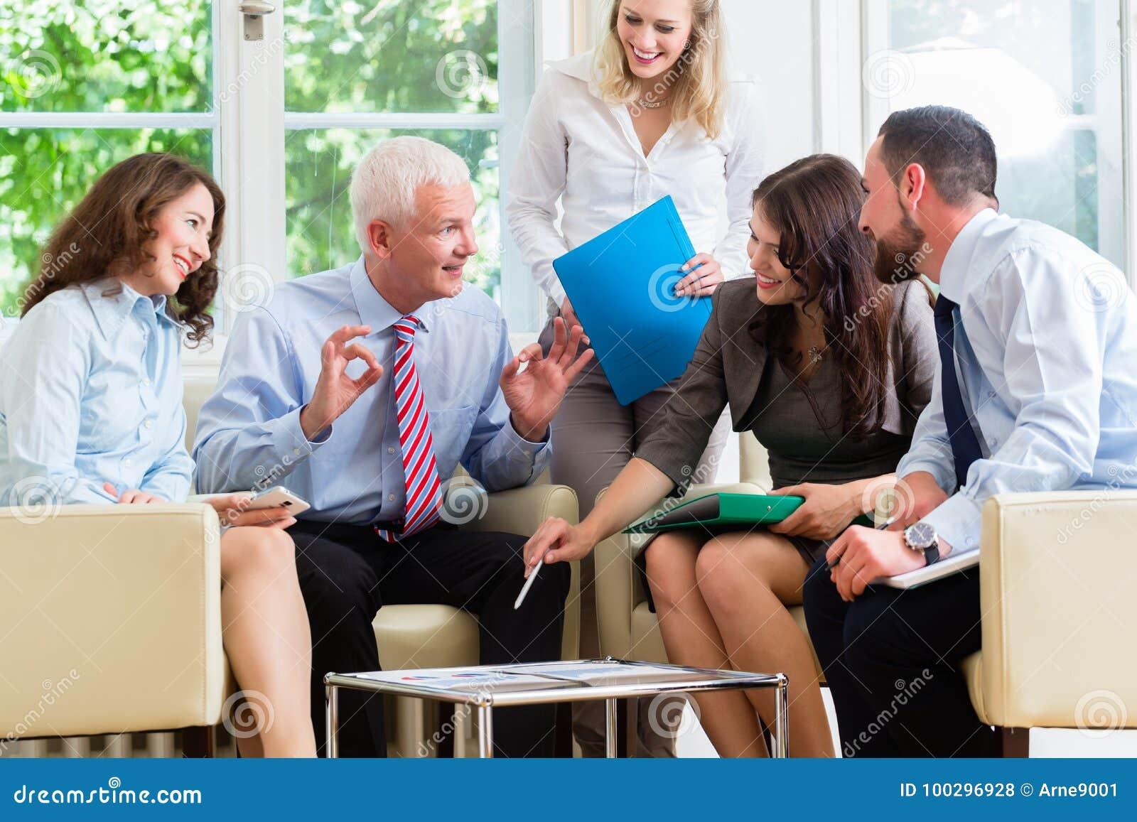 Pięć ludzi biznesu w drużynowych spotkania studiowania wykresach