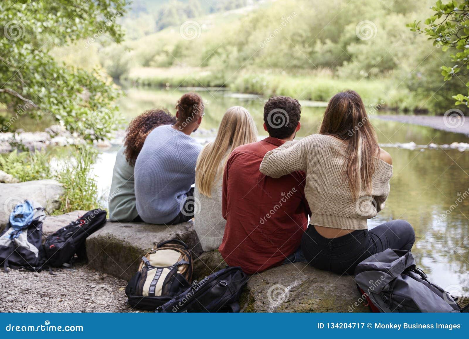 Pięć młodych dorosłych przyjaciół bierze przerwy obsiadanie na skałach strumieniem podczas podwyżki, tylny widok, zakończenie w g