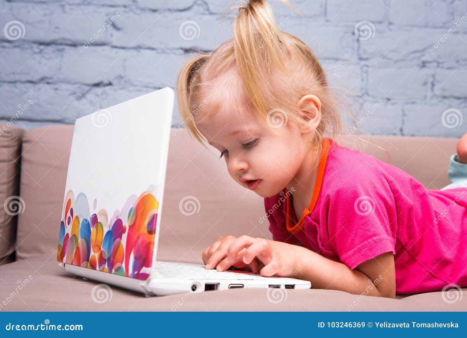 Piękna śmieszna blondynki dziewczyna dziecko dwa roku kłama na leżance indoors i używa białą laptop technologię z co