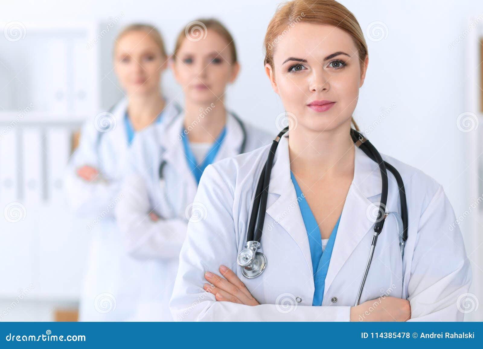 Piękna żeńska lekarz medycyny pozycja przy szpitalem przed medyczną grupą Lekarz przygotowywa pomagać pacjenta