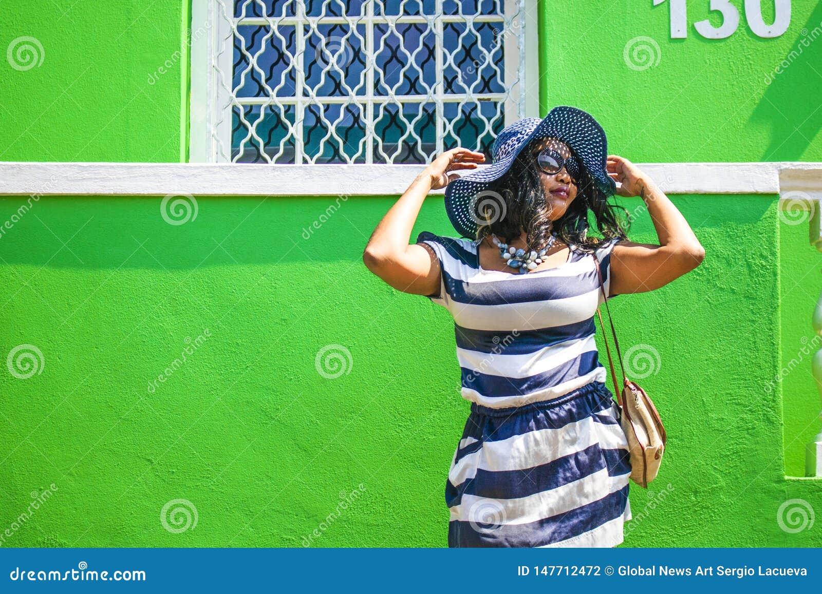 Piękna Afrykańska kobieta w błękitnej i białej pasiastej smokingowej modelacji przed tradycyjnym bo domem z zieleni ścianami - C