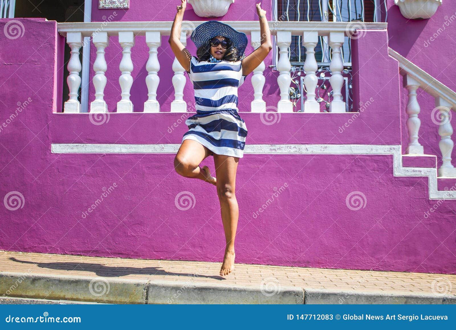 Piękna Afrykańska kobieta w błękitnym, białym pasiastym smokingowym doskakiwaniu przed tradycyjnymi domami z ścianami i Ka