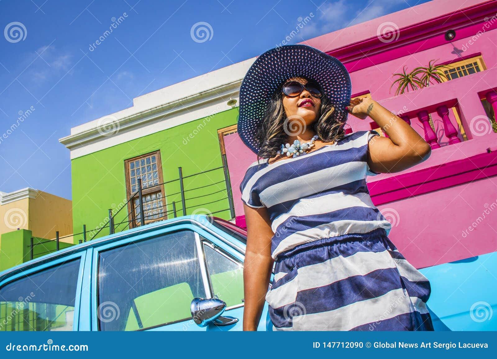 Piękna Afrykańska kobieta w bielu i błękitnym paskował suknię przed rocznika Ford Cortina tradycyjnymi domami bo i, C