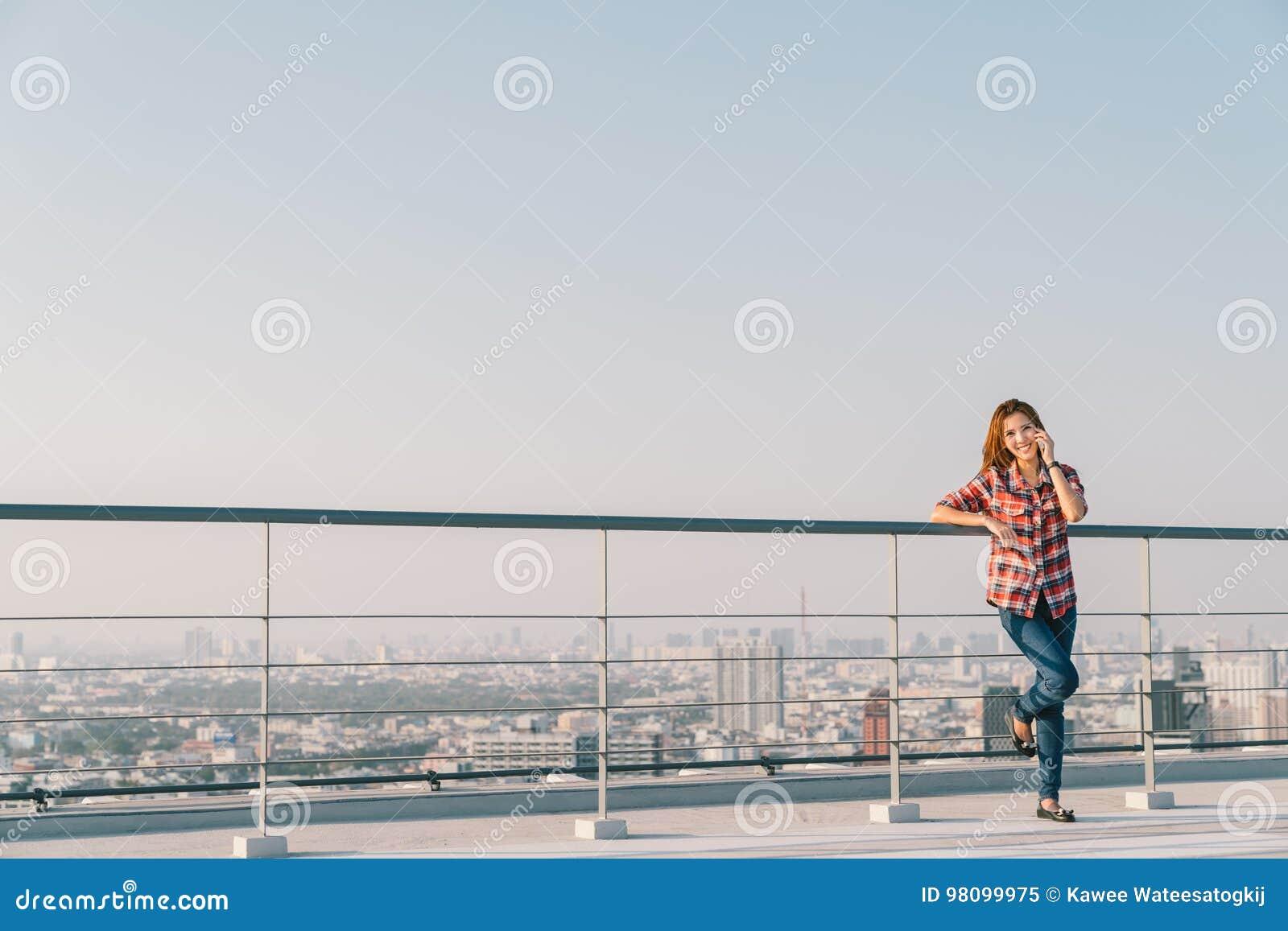 Piękna Azjatycka kobieta lub student collegu używa telefonu komórkowego wezwanie przy dachu samotnym lub osamotnionym w centrum p