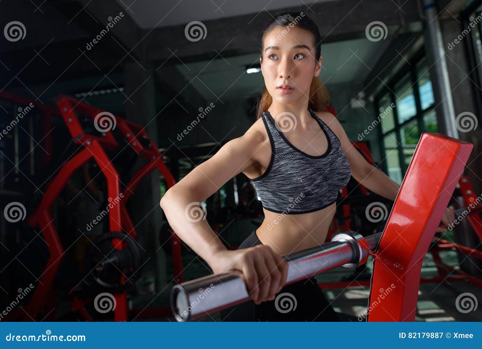 Piękna Azjatycka kobieta robi ćwiczeniom z barem w gym