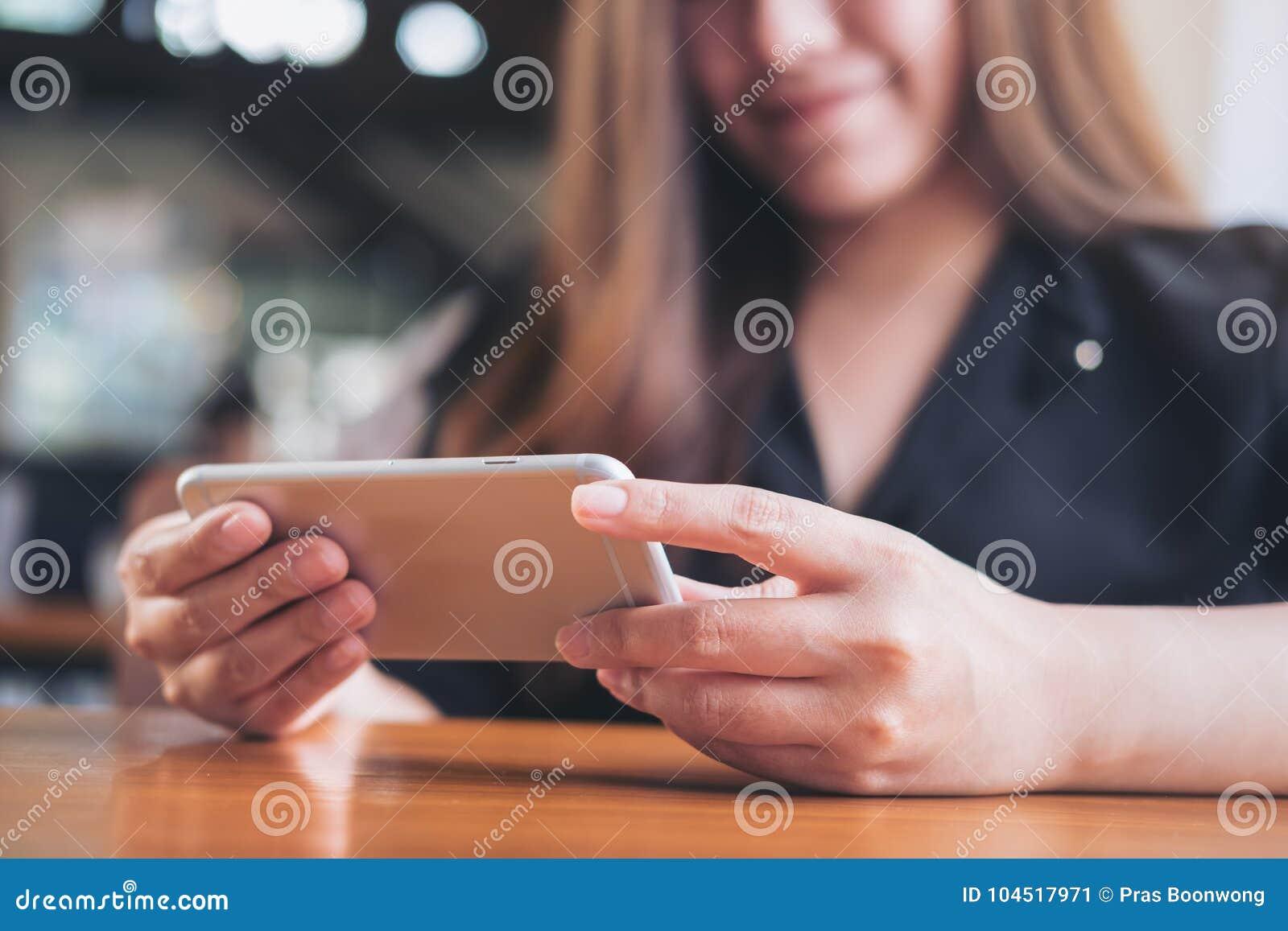 Piękna Azjatycka kobieta trzyma horyzontalnego mądrze telefon i używa z smiley twarzą oglądać tv i bawić się gry