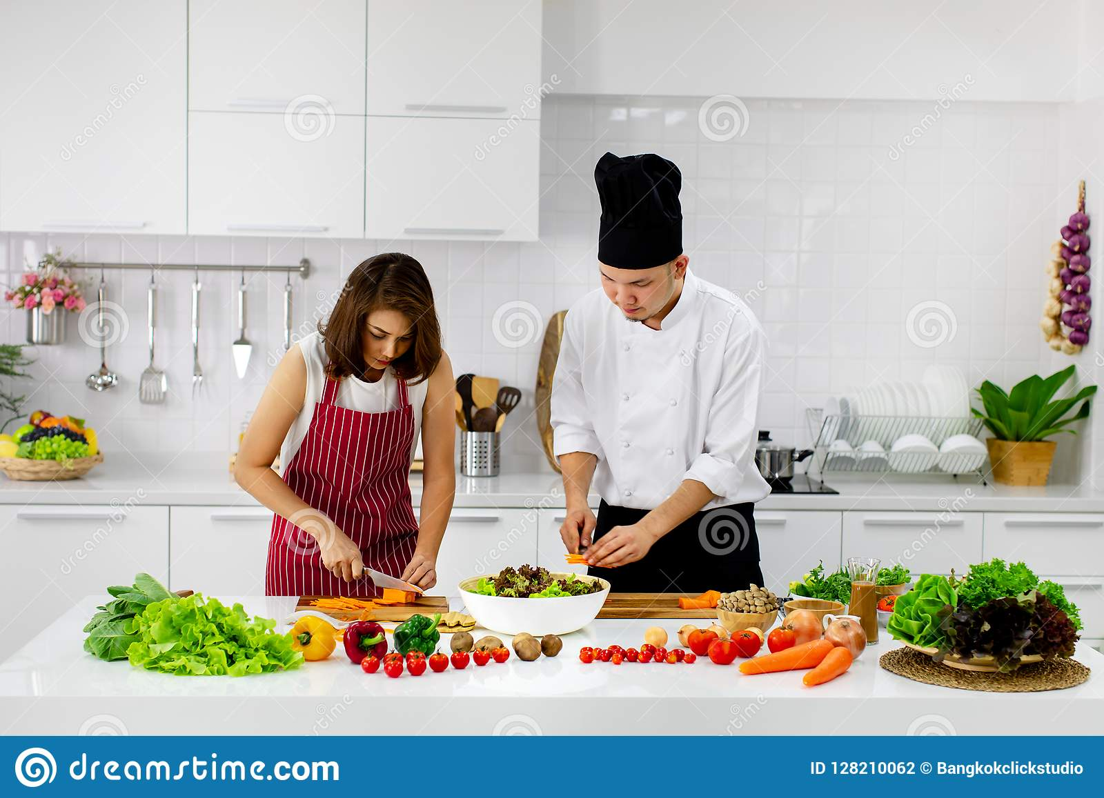 Piękna Azjatycka kobieta w czerwonym fartucha uczenie dlaczego gotować i mieszać