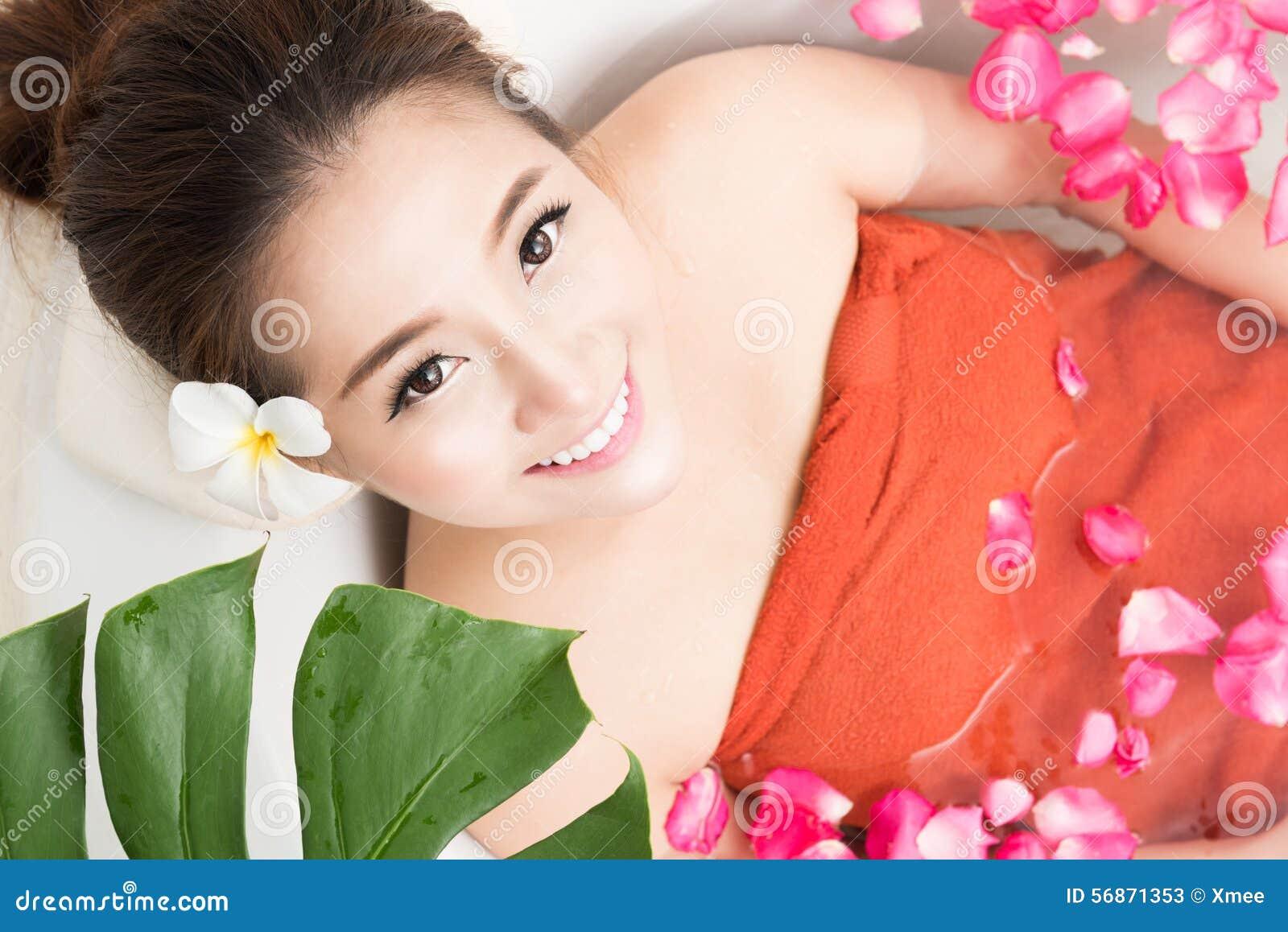 Piękna Azjatycka piękno kobieta w skąpaniu z różanym płatkiem Ciało zdrój i opieka