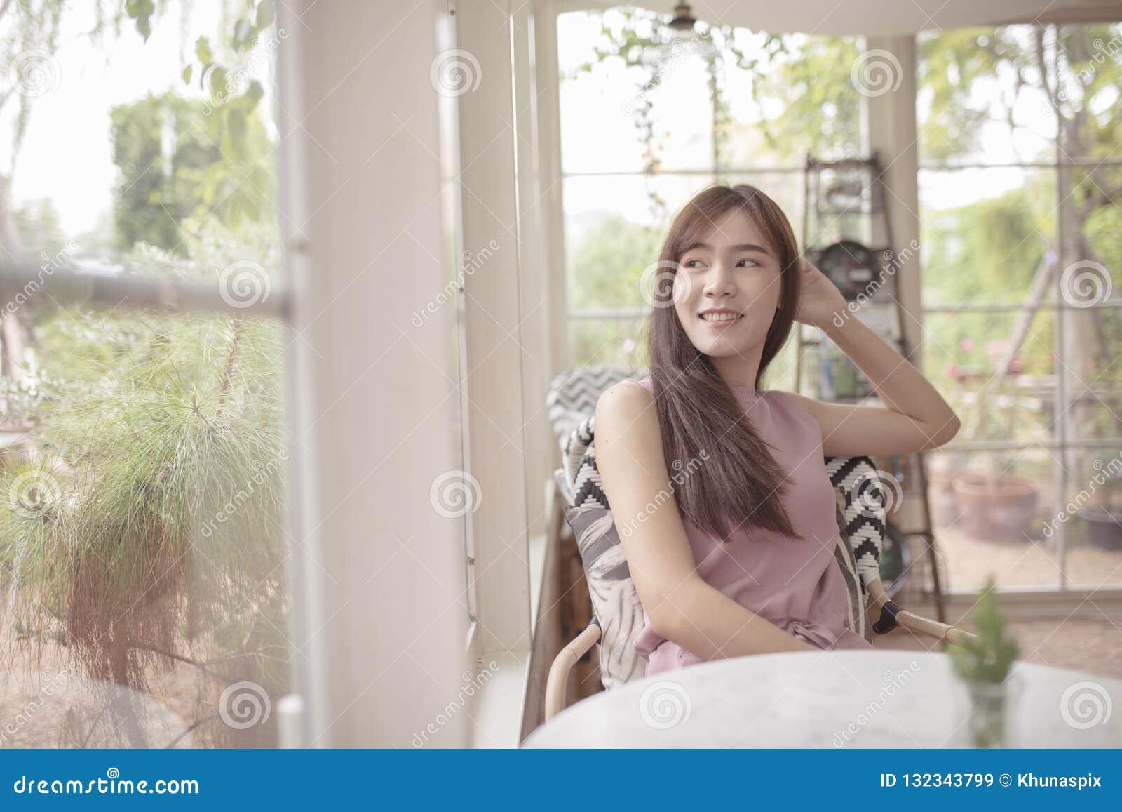 Piękna azjatykcia kobieta relaksuje w domowym żywym pokoju