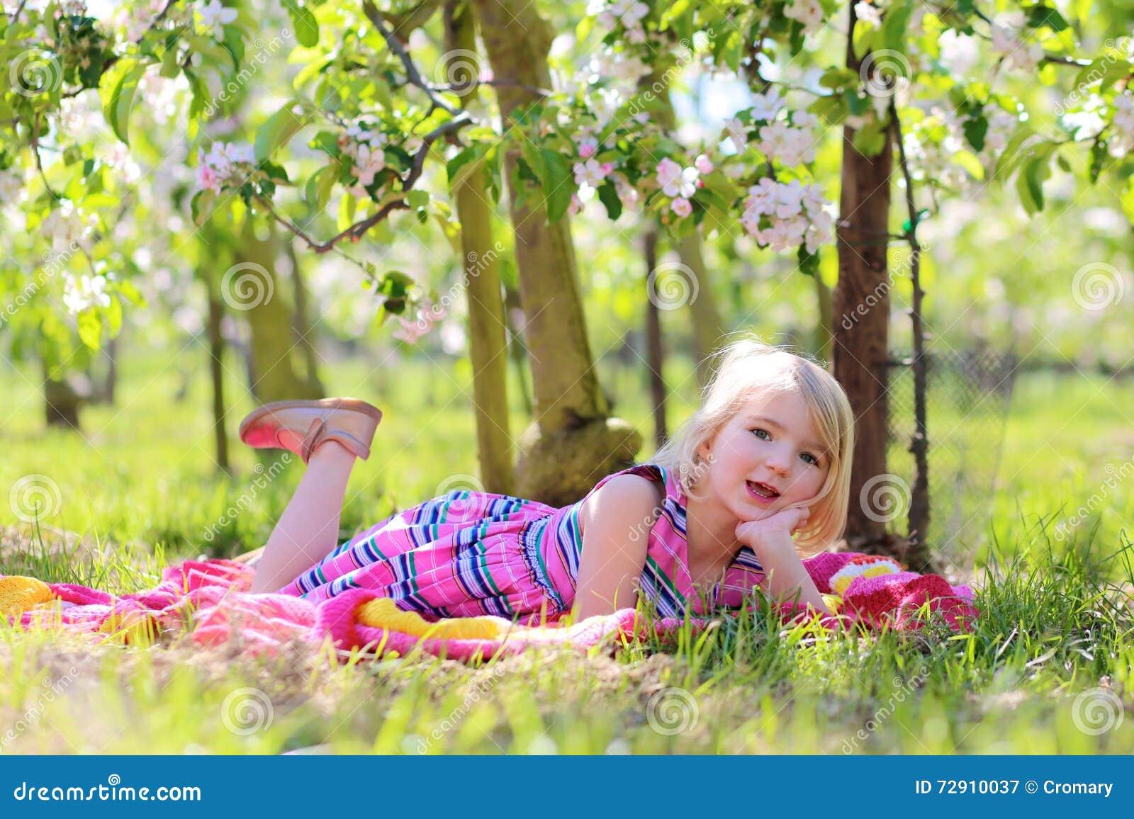 Piękna berbeć dziewczyna bawić się w kwitnąć owocowego orhcard