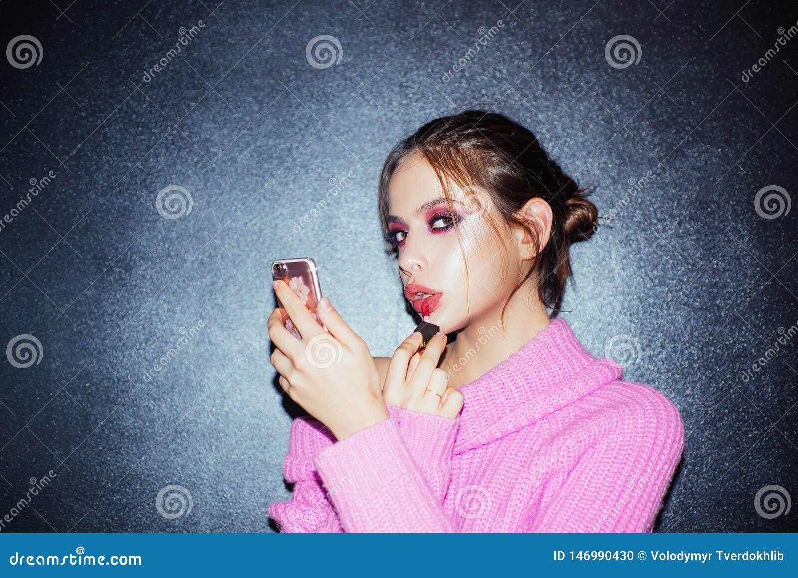 Piękna bloger Dziewczyna z pomadk? na wargach dziewczyna używa telefon jak lustro stawiający lipgloss Moda portret kobieta makeup