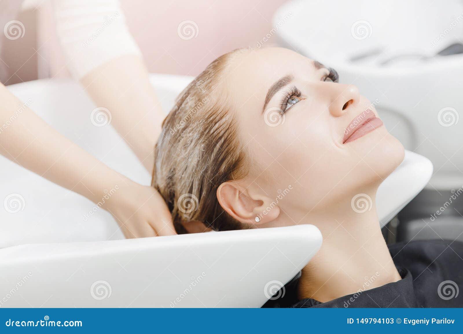 Piękna blond kobieta dostaje włosianego obmycie w piękno salonie Pojęcie głowy masaż