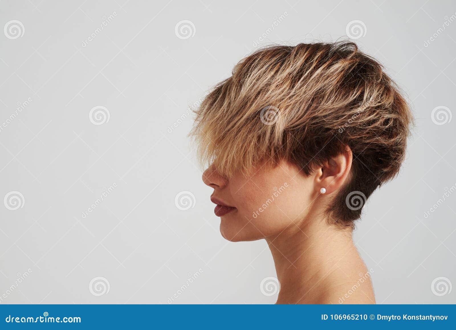 Piękna blond kobieta z krótką fryzurą pozuje przy studiiem