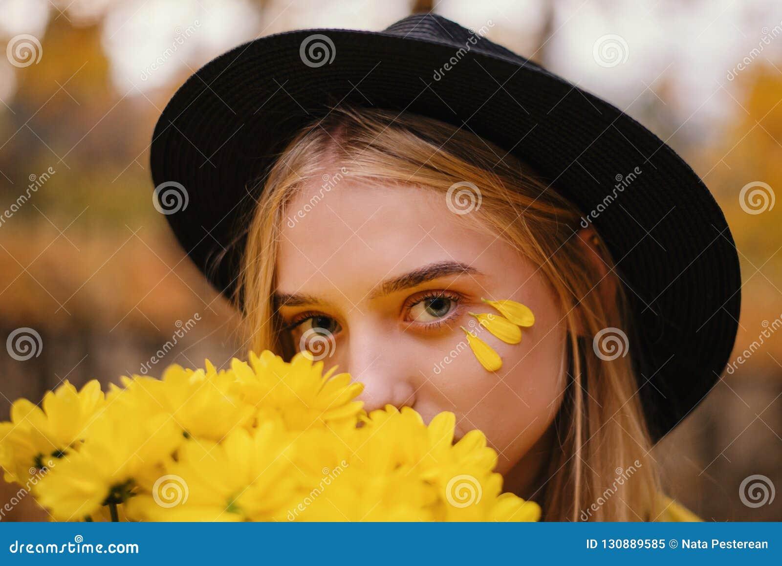 Piękna blondynki dziewczyna w kapeluszu z bukietem żółci kwiaty w jesień parku pełno żółci liście