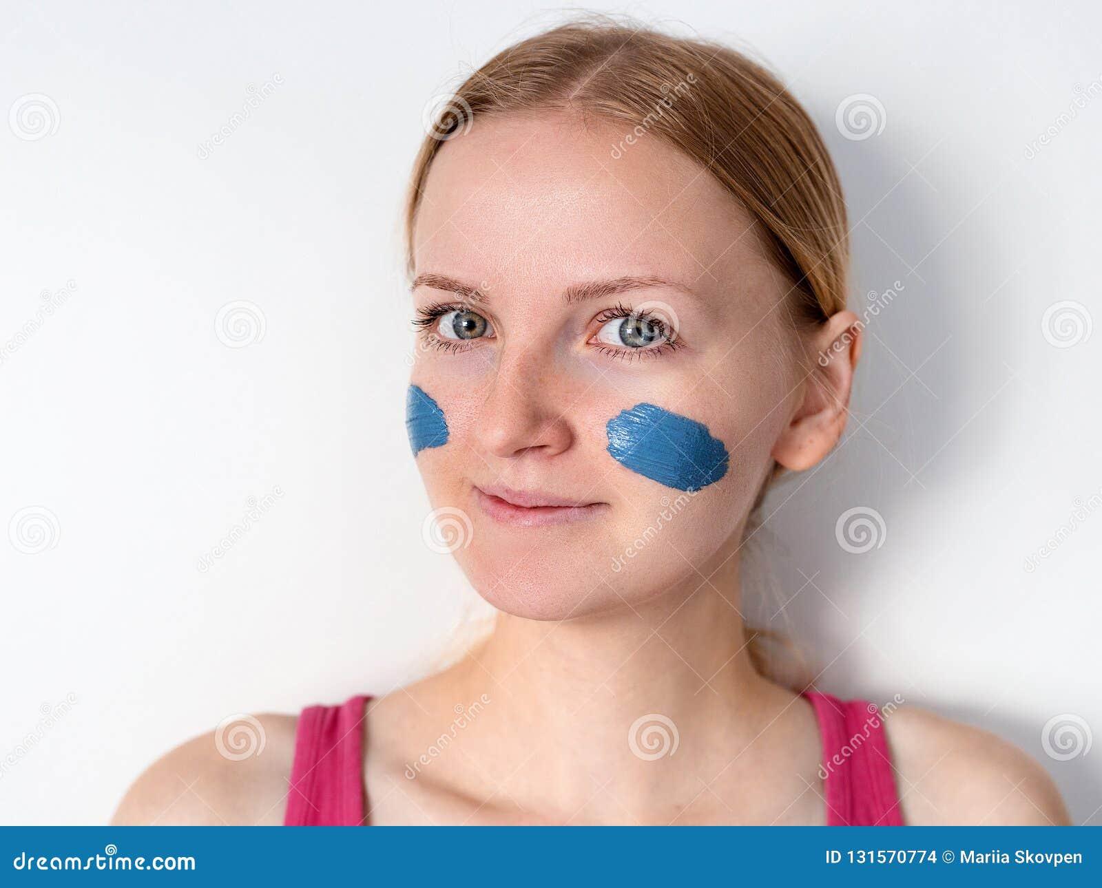 Piękna blondynki kobieta ma błękitną glinianą twarzową maskę stosuje beautician dziewczyna z maską na policzki jest uśmiechnięta
