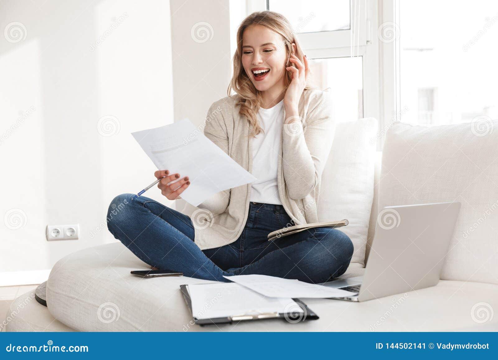 Piękna blondynki kobieta pozuje siedzieć indoors w domu używać laptop opowiada telefonem komórkowym