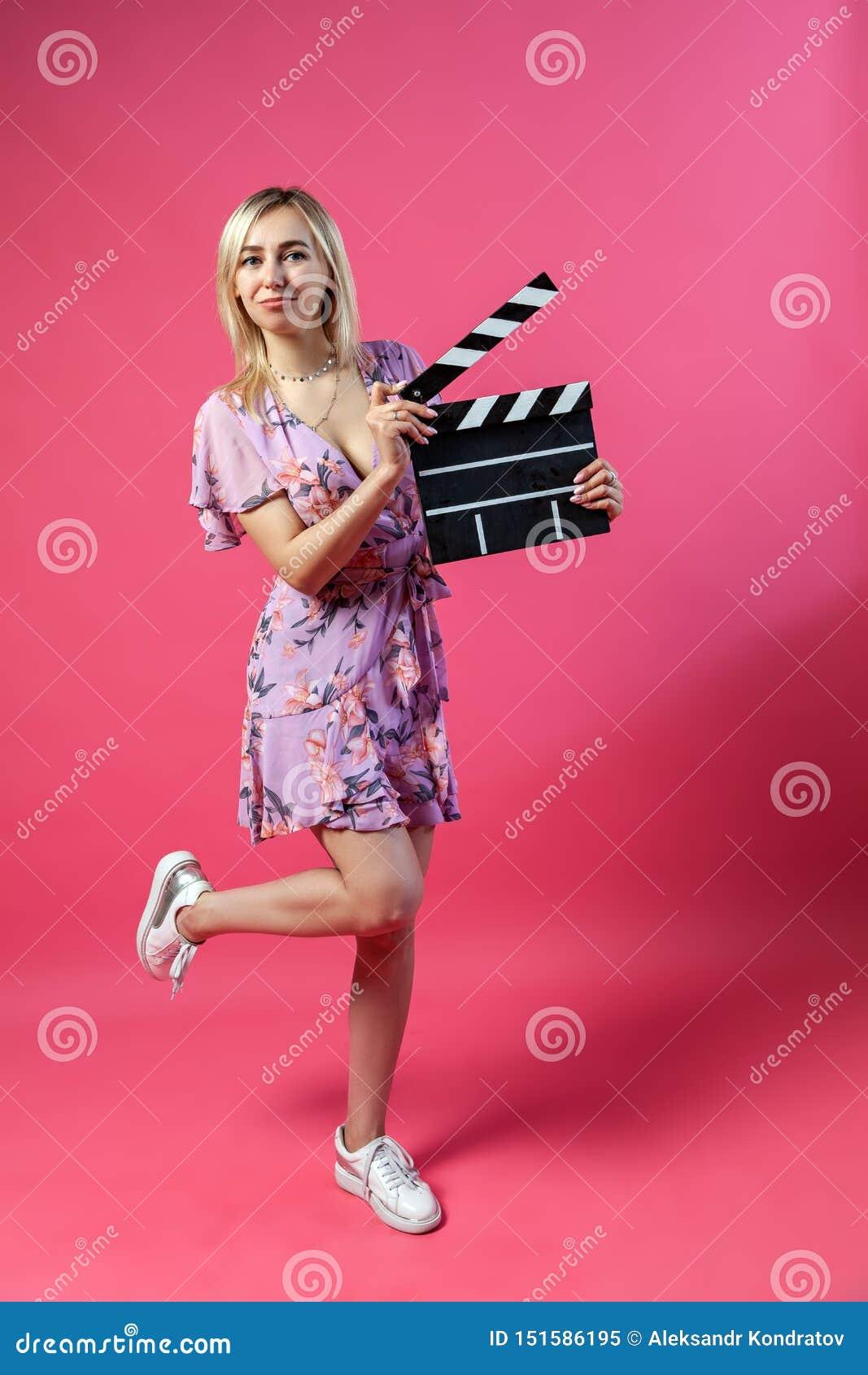 Piękna blondynki kobieta w purpurowi sundress trzyma otwartego clapperboard filmowa w czerni z białymi lampasami zaczynać strzela